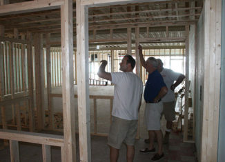 Rochester Opera House executive director Anthony Ejarque (left) and board president John McKenna (center) and a contractor observe the renovations underway at 32 North Main St., future site of the Rochester Performance & Arts Center.